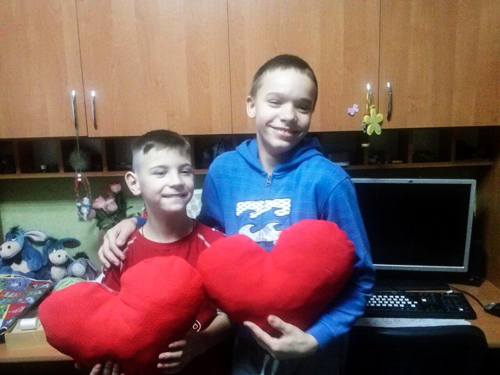 Twee jongens poseren met een zelfgemaakt hart